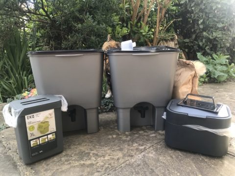 Two Bokashi bins with tops, two small food waste containers with a cat passing behind. The cat is shorter and longer than a Bokashi bin