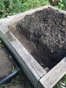 vegetable bed with soil removed from one quarter.