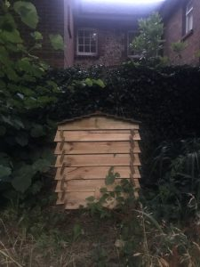 ooden compost bin shaped like a beehive.